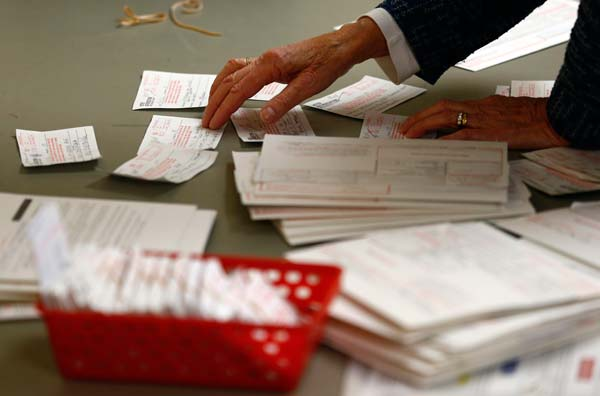 A poll worker looks at voter authorization forms and provisional ballots after the polls closed at the Covenant Presbyterian Church during the U.S. presidential election in Charlotte, North Carolina, November 6, 2012. REUTERS/Chris Keane