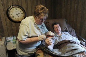 Kay Brubaker checks the blood sugar levels of her bed-ridden husband Larry, the victim of a stroke, at their home in Sunbury, Pennsylvania October 29, 2009. Credit: REUTERS/Brad Bower