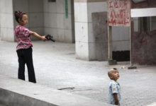 A Muslim girl points her toy pistol at boy in a Uighur neighbourhood of Urumqi in China's Xinjiang Autonomous Region July 10, 2009. Credit: REUTERS/Nir Elias