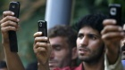 Kashmiri people use their mobile phones to take pictures during the funeral of Feroz Ahmad Malik in Palhalan, north of Srinagar September 6, 2010. REUTERS/Danish Ismail