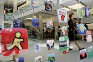 A woman walks past icons for Apple applications at the company's retail store in San Francisco, California, April 22, 2009. REUTERS/Robert Galbraith
