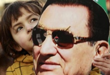 A child holds a mask of Egypt's former President Hosni Mubarak during a rally in Trafalgar Square, in central London February 12, 2011. REUTERS/Luke MacGregor 