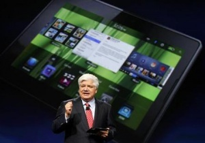 Mike Lazaridis, president and co-chief executive officer of Research in Motion, holds the new Blackberry PlayBook with a screen projection of the device as he speaks at the RIM Blackberry developers conference in San Francisco, California September 27, 2010. REUTERS/Robert Galbraith