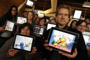 Nicholas Callaway, (R) founder of Callaway Digital Arts poses with members of his staff as they hold Apple Ipads displaying Ipad apps that they helped created and publish at the company's headquarters in lower Manhattan during an interview with Reuters in New York, in this picture taken March 7, 2011.