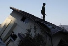 A member of the Japan Self Defense Force stands on a house at an area that was damaged by the March 11 earthquake and tsunami, in Yamada, Iwate prefecture April 5, 2011. REUTERS/Toru Hanai 
