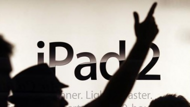 A shop assistant in Sydney gestures in front of an advertising sign moments before Apple's iPad 2 became available for direct purchase in Australia March 25, 2011.  REUTERS/Tim Wimborne