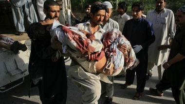 A hospital worker carries a man who was injured in a bomb attack at a paramilitary force academy in Charsadda, after he was brought to the Lady Reading hospital in Peshawar for treatment May 13, 2011. REUTERS/K. Parvez