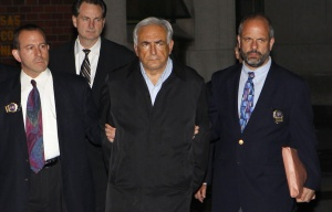 Dominique Strauss-Kahn (C), head of the International Monetary Fund (IMF), departs a New York Police Department precinct in New York late May 15, 2011.  A handcuffed IMF chief, Dominique Strauss-Kahn, facing charges he sexually assaulted a hotel maid, was escorted from a New York Police Department unit late on Sunday.   REUTERS/Mike Segar
