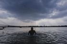 A devotee takes a dip against the backdrop of rain clouds in the waters of the river Ganges in Kolkata May 29, 2011. REUTERS/Rupak De Chowdhuri