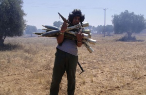A rebel poses with rocket-propelled grenades taken from an armoured personnel carrier (APC) captured from forces loyal to Libyan leader Muammar Gaddafi on the outskirts of the town of Zlitan, west of the rebel-held port city of Misrata June 10, 2011. Forces loyal to Gaddafi on Friday surrounded Zlitan, one of only three towns separating the rebel-held city of Misrata from the capital Tripoli, a rebel military spokesman said.     REUTERS/Abdelkader Belhessin