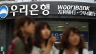 Japanese tourists walk in front of a branch of Woori Bank in Seoul August 23, 2010. REUTERS/Lee Jae-Won