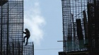 A worker climbs down a steel structure at a construction site in Jakarta May 4, 2011. REUTERS/Beawiharta