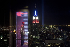 A reflection can be seen on a glass barrier in the Top Of The Rock observation deck in front of the Tribute in Light memorial shining behind the Empire State Building marking the ninth anniversary of the September 11 attacks on the World Trade Center in New York September 11, 2010.  REUTERS/Lucas Jackson