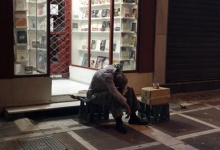 A homeless person sleeps outside a bookstore in central Athens August 20, 2011. REUTERS/Yiorgos Karahalis