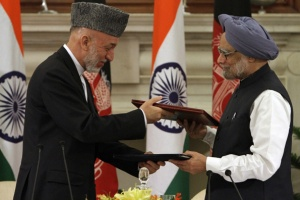 Afghanistan's President Hamid Karzai (L) and India's Prime Minister Manmohan Singh exchange documents after signing a joint statement at Hyderabad House in New Delhi October 4, 2011.    REUTERS/B Mathur