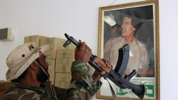 An anti-Gaddafi soldier breaks a picture frame holding a photo of Muammar Gaddafi inside Ibn Sina hospital in the centre of Sirte October 9, 2011. REUTERS/Thaier al-Sudani
