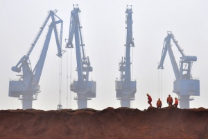 Workers remove covering from Australian iron ore at the port in Tianjin municipality in this March 29, 2010 file photo.   REUTERS/Vincent Du/Files