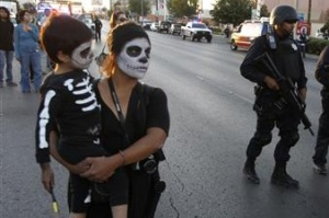 A woman holds her child during a protest in Ciudad Juarez November 1, 2011. Police arrested around 25 protesters as they were trying to put up crosses in a public area in representation of the thousands of victims of the drug war. REUTERS/Jose Luis Gonzalez