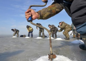 "Fishermen drill ice-holes during a competition in Russia's far eastern city of Vladivostok February 19, 2012. Participants of the contest, which was held during the ""People Fishing All-Russian Festival"" under the patronage of Russia's Prime Minister Vladimir Putin, competed against one another to drill ice-holes in the quickest time possible, according to organizers.  REUTERS/Yuri Maltsev  (RUSSIA - Tags: SOCIETY)"