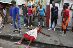 A reveller lays on the sidewalk during Jouvert celebrations in the capital of Trinidad and Tobago, February 20, 2012. REUTERS/Andrea De Silva
