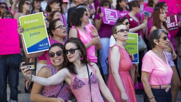 """Activists take a selfie during a rally in support of Planned Parenthood on """"National Pink Out Day"""" on the steps of City Hall in Los Angeles, California September 29, 2015. REUTERS/Mario Anzuoni"""