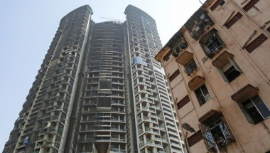 An under construction high-rise residential tower is pictured behind an old residential building in Mumbai, India, February 8, 2016. REUTERS/Danish Siddiqui