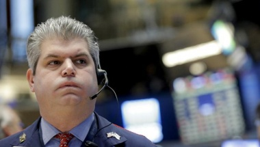 Traders work with a floor official on the floor of the NYSE
