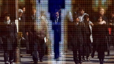 Pedestrians are reflected in an electronic board showing the graph of the recent fluctuations of the exchange rates between the Japanese yen against the U.S. outside a brokerage in Tokyo, Japan, February 4, 2016. REUTERS/Yuya Shino
