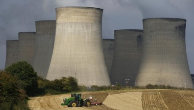 A farmer works a field in the shadows of Ratcliffe-on-Soar Power Station in central England, September 10, 2014.