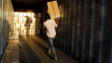 A worker loads goods into a container at Thar Dry Port in Sanand