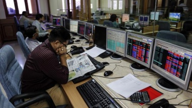 A broker reads a newspaper while trading at a brokerage firm in Mumbai May 14, 2014. REUTERS/Danish Siddiqui/Files