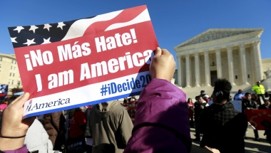 A protester holds a sign as immigrants and community leaders rally in front of the Supreme Court to mark the one-year anniversary of Obama's executive orders on immigration in Washington, in this file photo taken Nov 20, 2015. REUTERS/Kevin Lamarque/Files