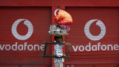 """Vendor selling """"paani puri"""", a traditional Indian snack, walks past closed shops displaying an advertisement for Vodafone in Jammu May 22, 2012. REUTERS/Mukesh Gupta/File photo"""