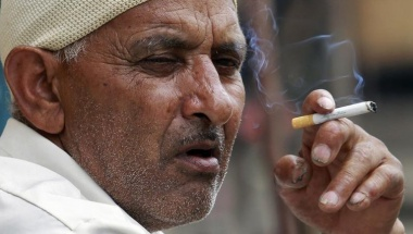 A man smokes a cigarette as he sits on a pavement along a road in Srinagar September 4, 2012. Reuters/Fayaz Kabli/Files