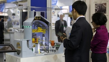 Visitors look at a nuclear power plant station model by American company Westinghouse at the World Nuclear Exhibition 2014, the trade fair event for the global nuclear energy sector, in Le Bourget, near Paris October 14, 2014. REUTERS/Benoit Tessier/Files