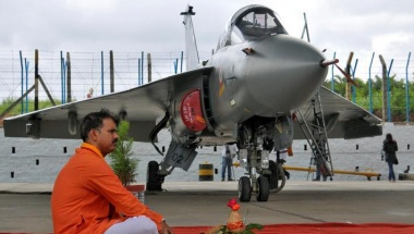 A Hindu priest waits to perform prayers next to Tejas, India's first locally-built Light Combat Aircraft, before its induction into the Indian Air Force at the Hindustan Aeronautics Limited Airport in Bengaluru, July 1, 2016. REUTERS/Abhishek N. Chinnappa
