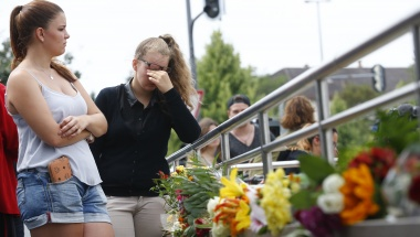Young women look at floral tributes near the Olympia shopping mall, where yesterday's shooting rampage started, in Munich, Germany July 23, 2016. REUTERS/Arnd Wiegmann
