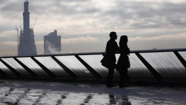 Construction takes place on The Shard building (at rear) as visitors pose on the balcony at One New Change shopping mall in London November 16, 2010. REUTERS/Suzanne Plunkett