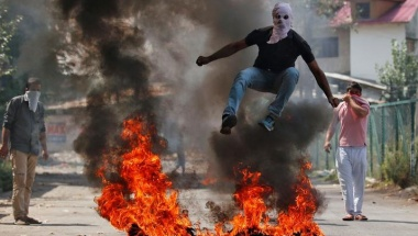 A man in a balaclava jumps over burning debris during a protest against the recent killings in Kashmir, in Srinagar, India September 12, 2016. REUTERS/Danish Ismail/File Photo