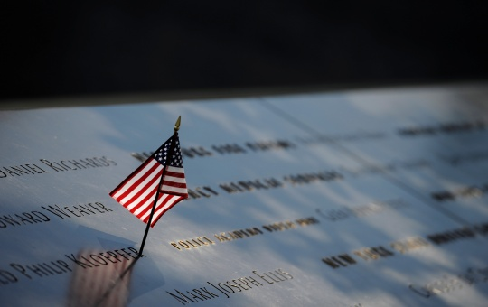 A woman lays her head on a row of names at the National September 11 Memorial in Manhattan. REUTERS/Mark Kauzlarich