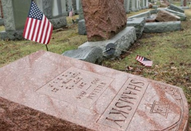 An American flag still stands next to one of over 170 toppled Jewish headstones after a weekend vandalism attack on Chesed Shel Emeth Cemetery in University City, a suburb of St Louis, Missouri, February 21, 2017.  REUTERS/Tom Gannam