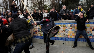 A demonstrator in support of U.S. President Donald Trump swings a stick towards a group of counter-protesters during a 'People 4 Trump' rally in Berkeley, California March 4, 2017. REUTERS/Stephen Lam