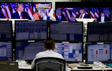 An employee of a foreign exchange trading company works near monitors showing U.S. Donald Trump speaking on TV (top) in Tokyo, Japan, November 9, 2016. REUTERS/Toru Hanai/File Photo