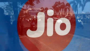 Commuters are reflected on an advertisement of Reliance Industries' Jio telecoms unit, at a bus stop in Mumbai, February 21, 2017. REUTERS/Shailesh Andrade/Files