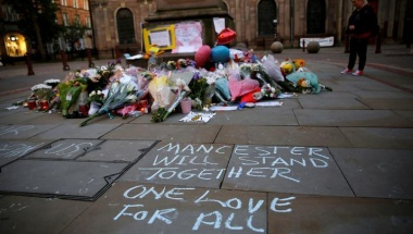 A woman looks at flowers for the victims of the Manchester Arena attack, in central Manchester Britain May 23, 2017. REUTERS/Stefan Wermuth