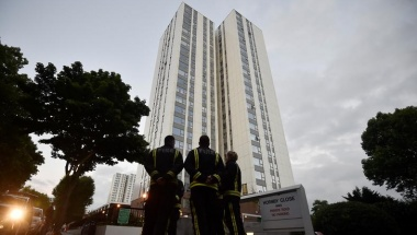Firefighters stand outside the Burnham Tower residential block, as residents were evacuated as a precautionary measure following concerns over the type of cladding used on the outside of the building on the Chalcots Estate in north London, Britain, June 24