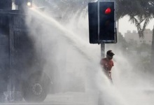 An anti-government protester stands behind a traffic light as he is sprayed with water in the village of Jidhafs, west of Manama, February 20, 2012. REUTERS/Hamad I Mohammed
