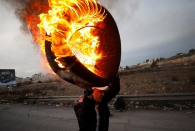 A Palestinian holds a burning tire during clashes with Israeli troops at a protest against U.S. President Donald Trump's decision to recognize Jerusalem as Israel's capital, near the Jewish settlement of Beit El.  REUTERS/Mohamad Torokman