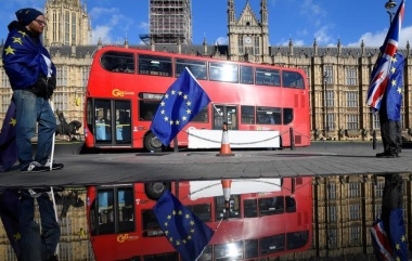 Anti-Brexit demonstrators waving EU and Union flags are reflected in a puddle in front of the Houses of Parliament in London, Britain, March 28, 2018. REUTERS/Toby Melville