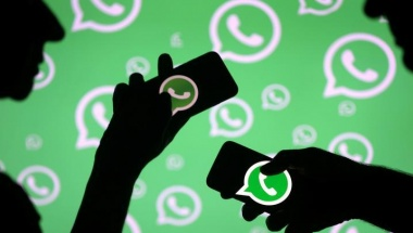 Men pose with smartphones in front of displayed Whatsapp logo in this illustration September 14, 2017. REUTERS/Dado Ruvic/Files